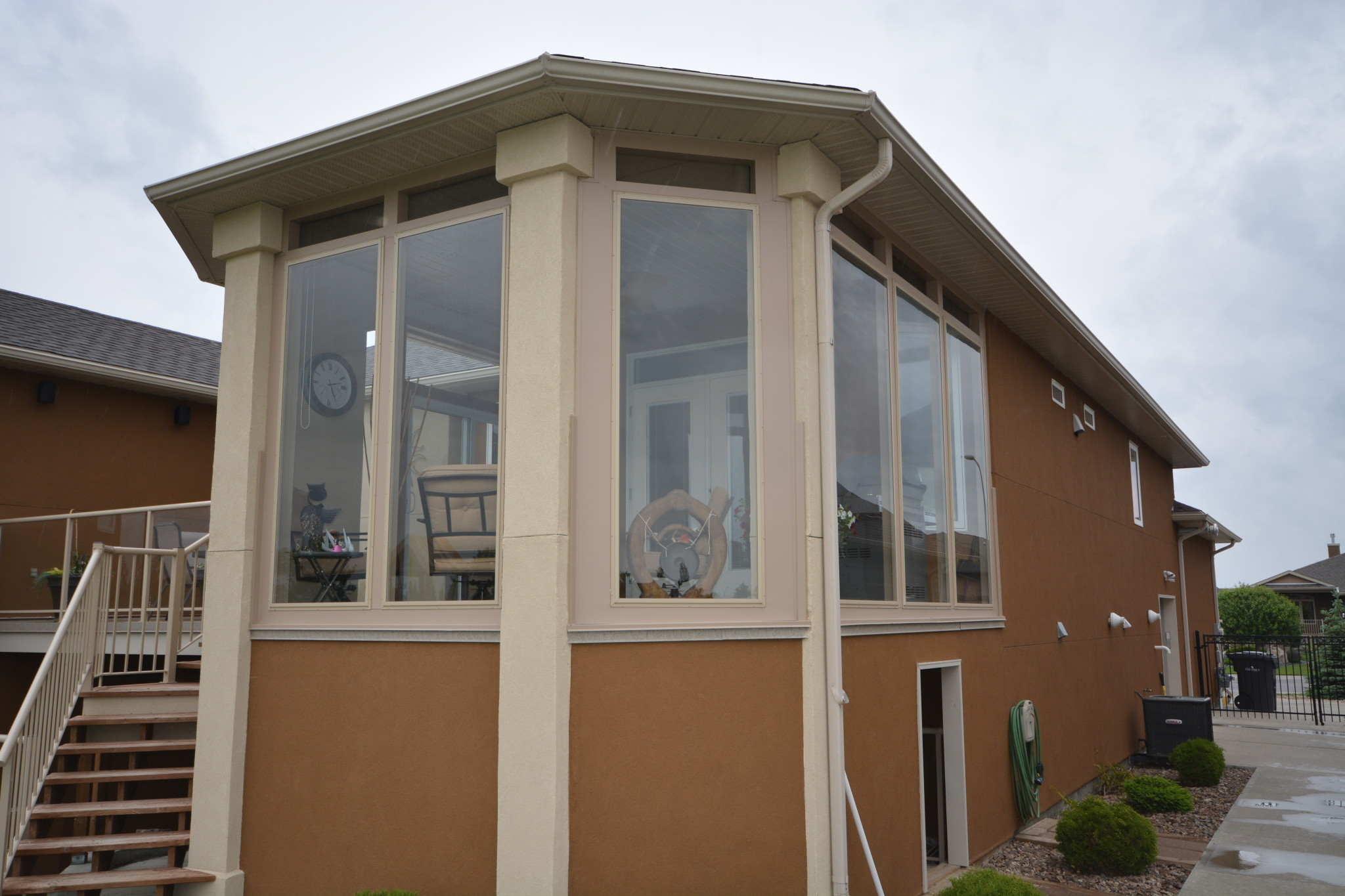 Alta Aluminum Sunroom attached to a brown house with a big deck