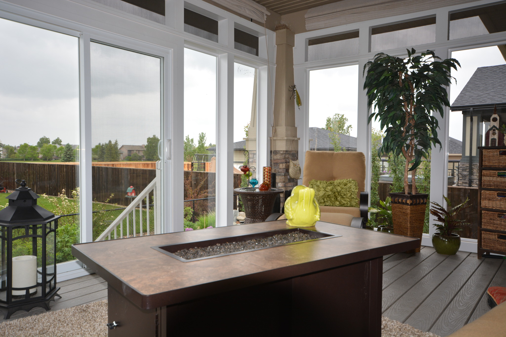 Sunroom with a fireplace in the middle, and a glass door to the backyard