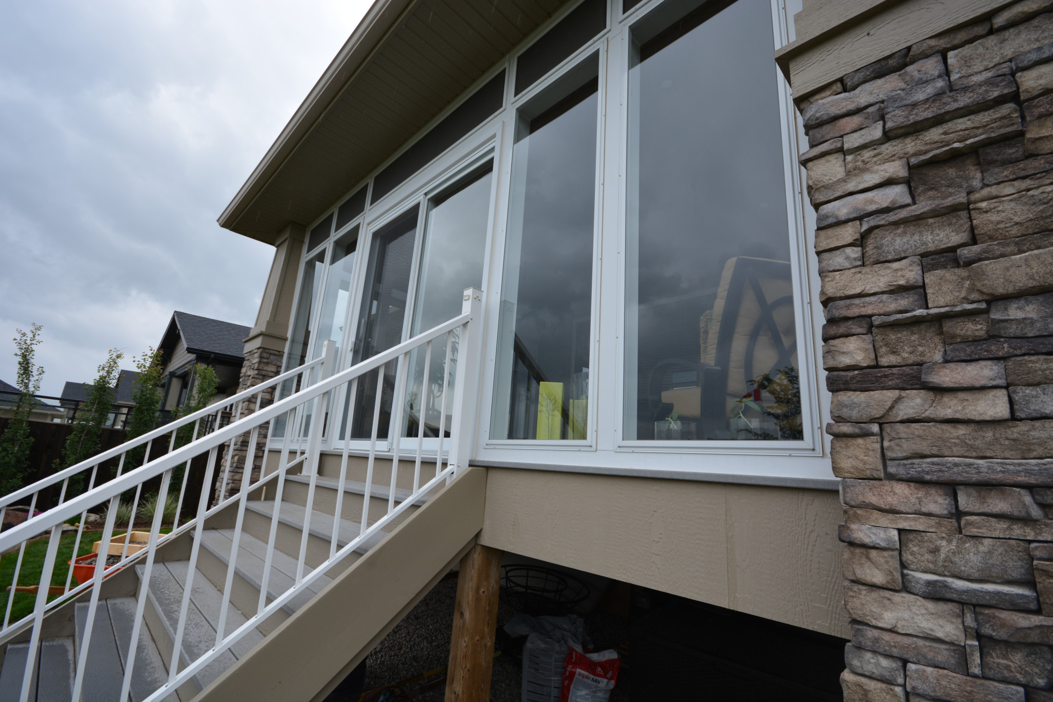 Alta Aluminum Sunroom with a white metal railing leading to a backyard